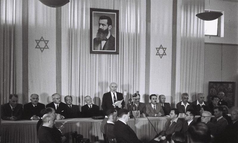 رئيس وزراء إسرائيل الأول ديفيد بن غوريون يقرأ إعلان استقلال إسرائيل وهو يقف أمام صورة لتيودور هيرتزل - 14 أيار 1948 (رويترز)
