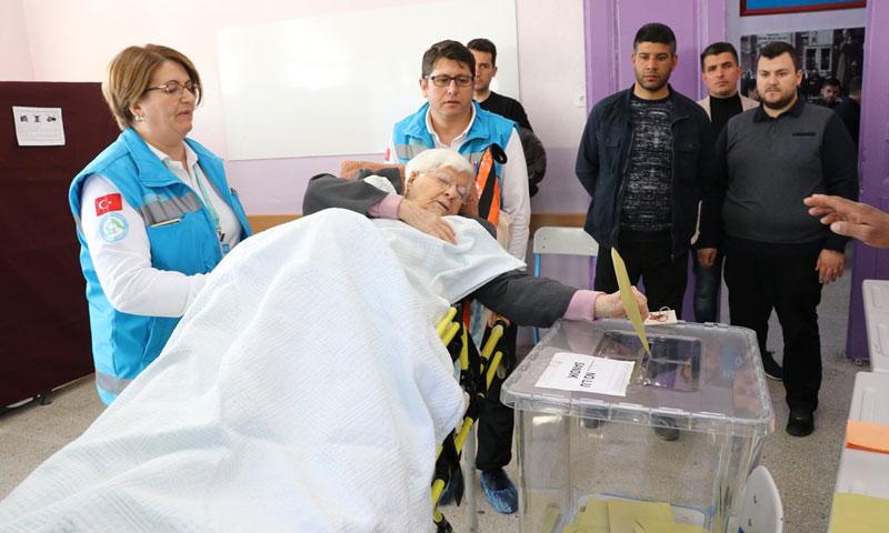 مسعفون ينقلون ناخبة مريضة إلى مراكز الاقتراع للإدلاء بصوتها في الانتخابات المحلية التركية - 31 آذار 2019 (TRT)