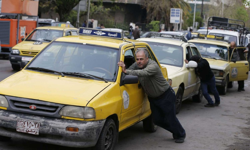 سائقي سيارات الأجرة يدفعون سياراتهم التي نفدت فيها البنزين إلى محطة للبنزين في العاصمة السورية دمشق في 16 أبريل 2019 - (AFP)