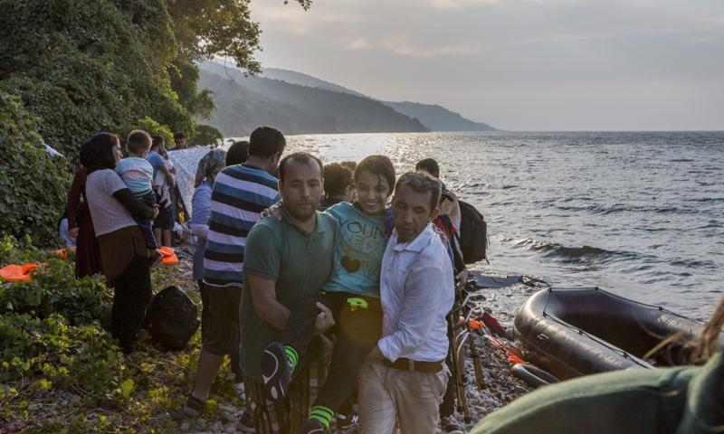 نوجين، البالغة وقتها من العمر 16 عاماً، محمولة بعد أن تم إنقاذها من قارب هش قرب جزيرة ليسفوس اليونانية (UNHCR)