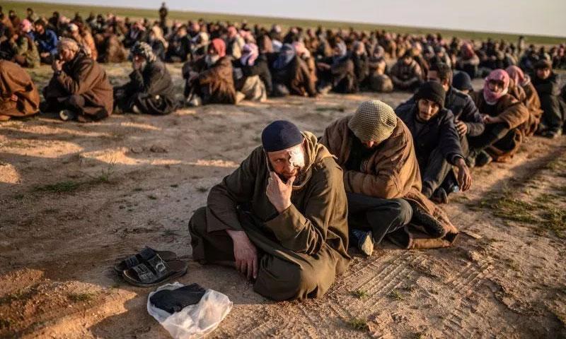 رجال يشتبه بانضمامهم لتنظيم الدولة الإسلامية بانتظار أن يتم تفتيشهم من قبل قوات سوريا الديمقراطية عقب مغادرتهم للباغوز - 22 من شباط 2019 (AFP)