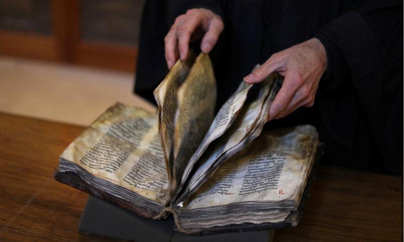 الأب جاستين قيم مكتبة دير القديسة كاثرين في سيناء يقلب صفحات مخطوطة قديمة - 6 آذار 2019 (رويترز)