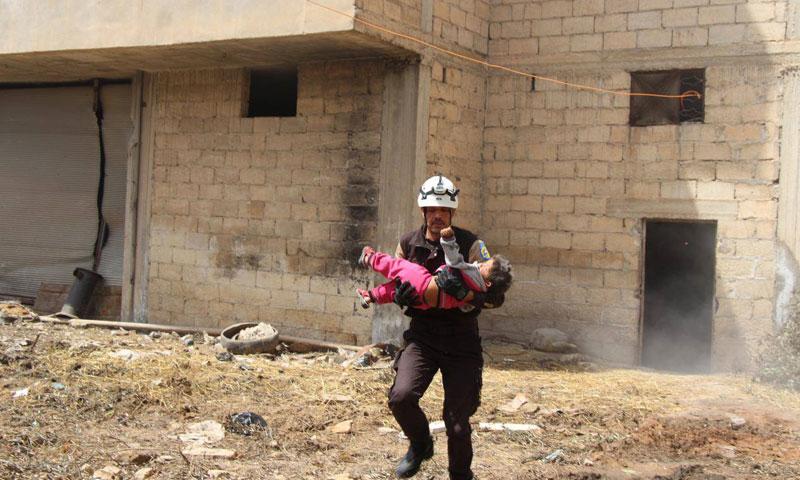 عناصر الدفاع المدني يخلون النساء والأطفال في مدينة خاون شيخون جنوبي إدلب أثناء تعرضها لقصف صاروخي من قوات الأسد 25 نيسان 2019 (الدفاع المدني السوري)