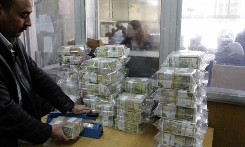 موظف يقوم بتغليف ليرات سورية في البنك المركزي بدمشق (رويترز)