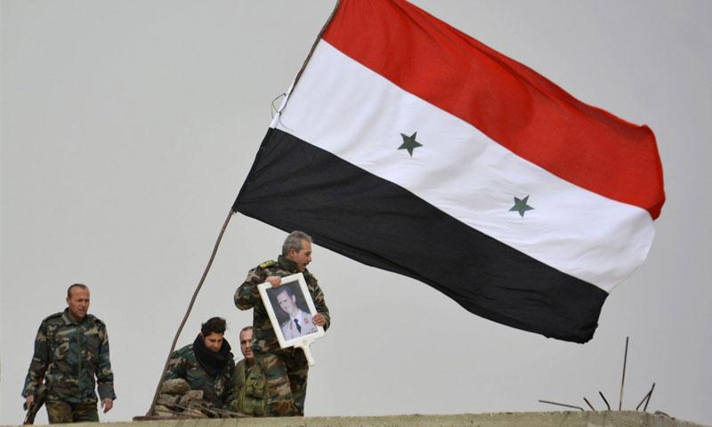 مقاتلون يرفعون صورة رئيس النظام السوري بشار الأسد بعد السيطرة على تل العدس بريف دمشق - 10 شباط 2015 (روتيزر)