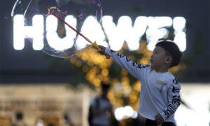 طفل يلعب بالفقاعات الصابونية أمام شعار شركة هواوي في بكين - 20 أيار 2019 (AP)