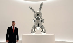 منحوتة أرنب للأمريكي جيف كونس والتي بيعت بمبلغ 91.1 مليون دولار يقف بجانبها رجل أمن في دار المزاد كريتسيز في نيويورك - 15 أيار 2019 (AFP)