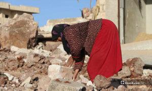 امراة بين ركام منزلها بعد قصفه بغارة روسية في كفرنبل بريف إدلب - 20 من أيار 2019 (عنب بلدي)