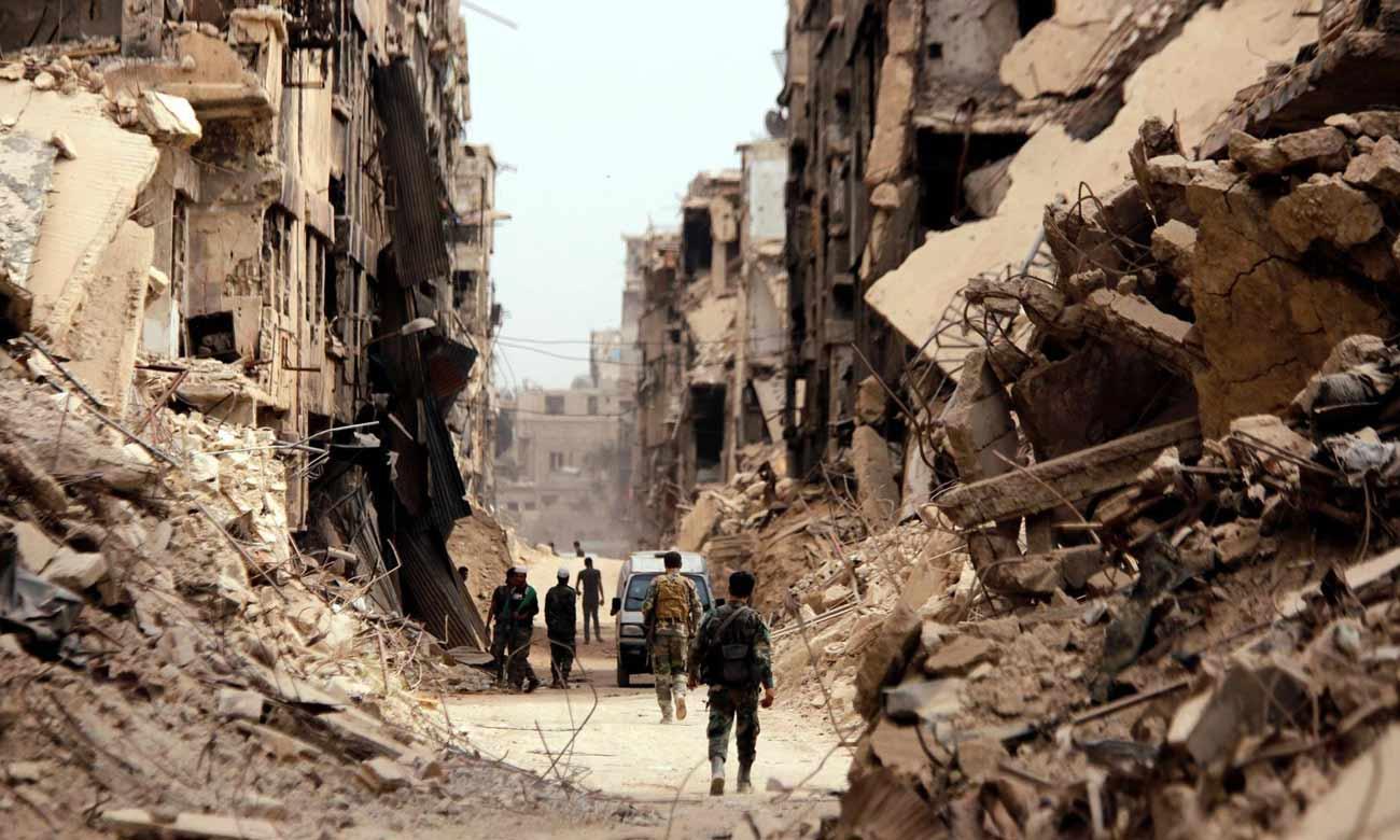 جنود تابعون للنظام السوري يسيرون وسط مخيم اليرموك جنوبي العاصمة السورية دمشق- آب 2018 (رويترز)