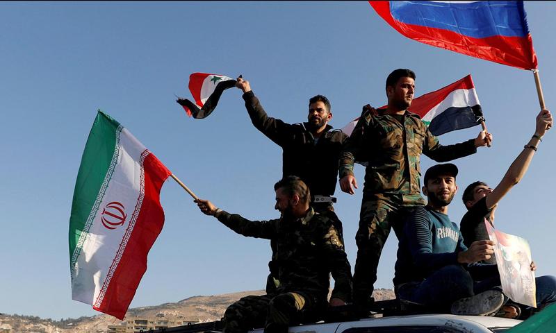 قوات سورية ترفع العلم الإيراني والروسي وعلم النظام السوري (رويترز)