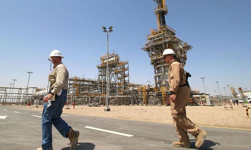 عامل عراقي مع عامل أجنبي من شركة إكسون موبيل قرب البصرة (رويترز)