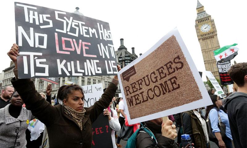 """متظاهرون يطالبون الحكومة البريطانية باستقبال المزيد من اللاجئين يحملون لافتة """"أهلا باللاجئين"""" و""""هذا النظام لا يعرف الحب إنه يقتلنا"""" - 2016 (AP)"""