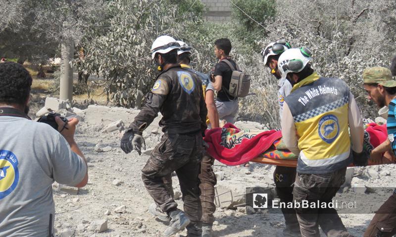 عناصر من الدفاع المدني يخلون ضحايا جراء القصف الذي استهدف بلدة الفطيرة جنوبي إدلب- 15 من حزيران 2019 (عنب بلدي)