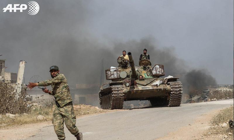 عناصر من الجبهة الوطنية للتحرير في أثناء توجههم للمشاركة في معركة بريف حماة الشمالي - 6 من حزيران 2019 (AFP عمر حاج قدور)