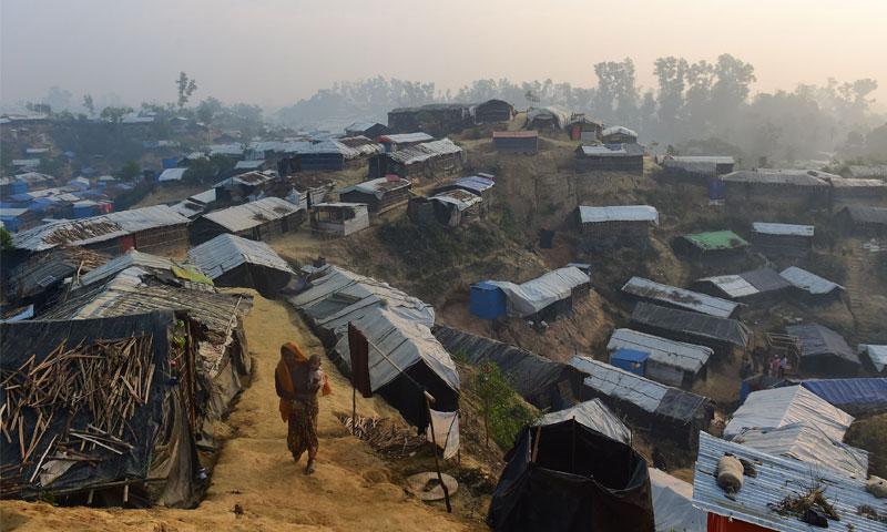 امرأة من الروهينغا تمشي ضمن مخيم للاجئين في بنغلاديش (AFP)