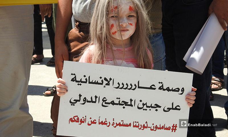 طفلة تشارك في مظاهرات ريف حلب تنديدًا بالقصف الروسي على إدلب - 26 من تموز 2019 (عنب بلدي)