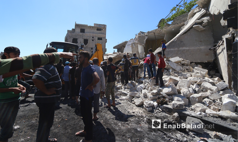 فرق الدفاع المدني في أثناء انتشال المدنيين من تحت أنقاض المنازل السكنية الت تعرضت لقصف جوي روسي في بلدة أورم الجوز بريف إدلب الجنوبي- 21 تموز 2019 (عنب بلدي)