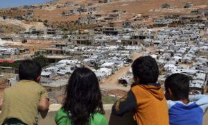 أطفال لبنانيون ينظرون إلى مخيمات السوريين في بلدية عرسال - 19 حزيران 2019 (AP)