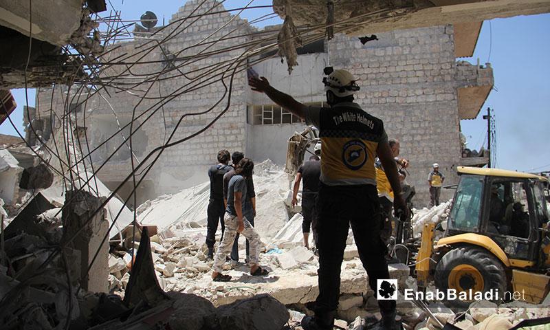 عناصر الدفاع المدني أثناء انتشال  مدنيين عالقين تحت أنقاض المنازل بعد تعرضها لغارات روسية في معرة النعمان جنوب إدلب 22 تموز 2019(عنب بلدي)