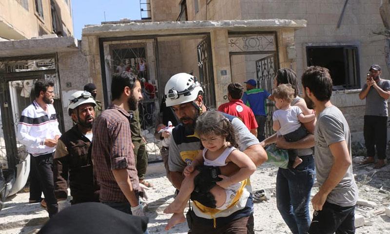 عناصر من الدفاع المدني يسعفون مدنيين تعرضوا لقصف جوي في حي القصور بمدينة إدلب 12 من تموز 2019 (الدفاع المدني السوري)
