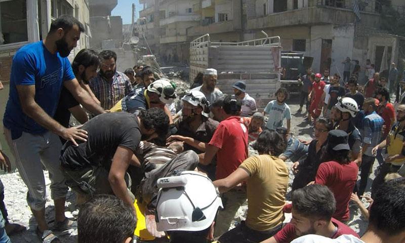 الدفاع المدني يسعف مدنيين تعرضت أحياؤهم لغارات صاروخية مكثفة من الطيران الحربي في مدينة أريحا جنوبي إدلب- 28 من تموز 2019 (الدفاع المدني السوري)