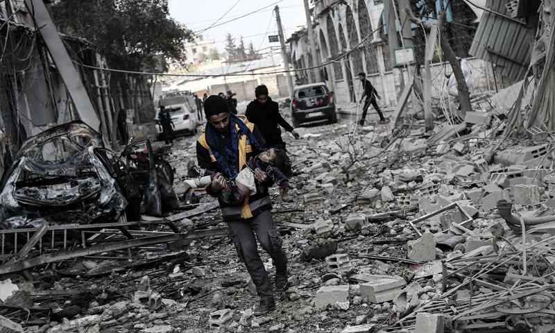 عنصر من الدفاع المدني يسعف طفلة في بلدة حمورية بالغوطة الشرقية أصيبت بالقصف (AFP)