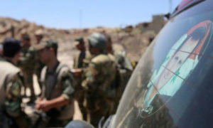عناصر من قوات الاسد أمام صورة رئيس النظام السوري بشار الأسد على سياراة (AFP)