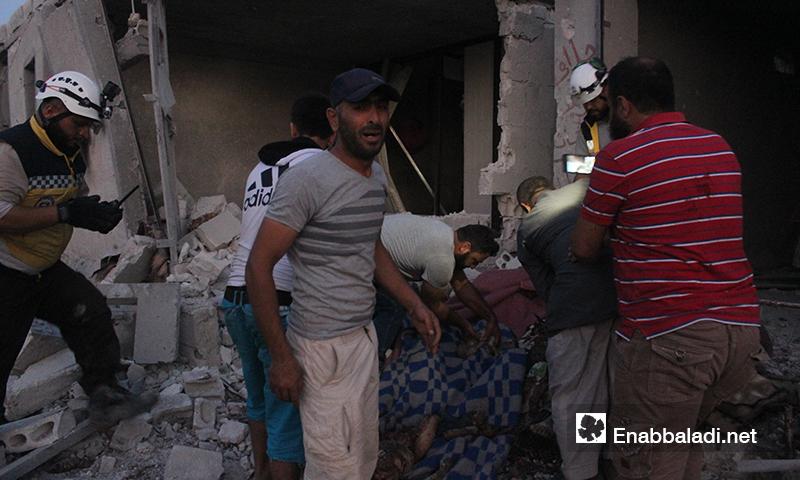 انتشال مدنيين من تحت أنقاض المنازل في تجمع للنازحين بعد تعرضهم لغارات روسية في بلدة حاس بريف إدلب الجنوبي 16 آب 2019 (عنب بلدي)