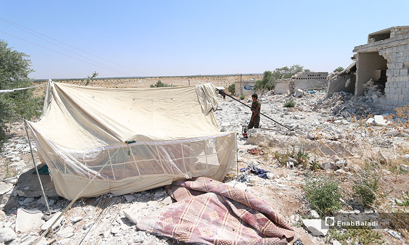 جمال الشمعة يبني خيمة فوق أنقاض منزله التي دمرته طائرات النظام المروحية في ريف إدلب الجنوبي - 6 من آب 2019 (عنب بلدي)