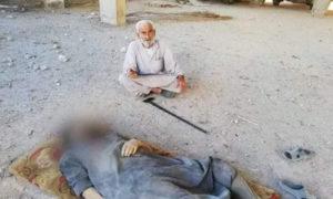 التسعيني قنبر البيوش يجلس قبالة جثمان ابنه نهاد في كفرنبل بريف إدلب - (فيس بوك)