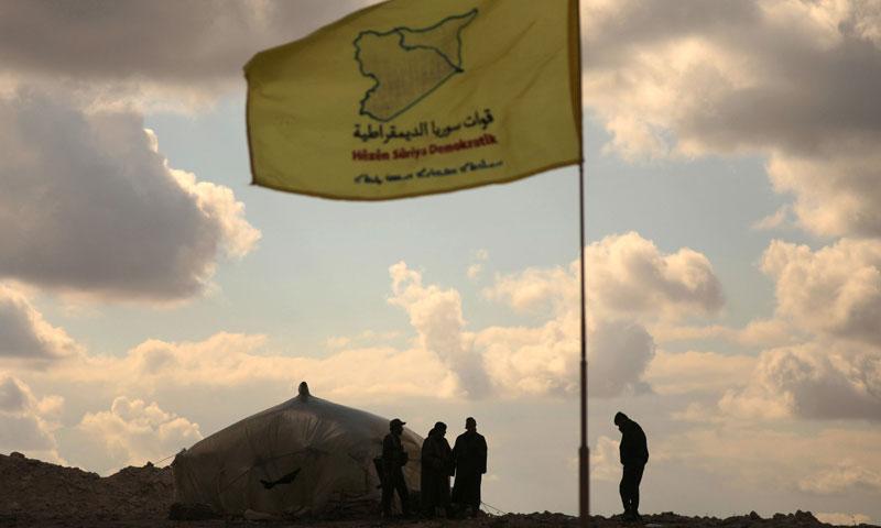عناصر من قوات سوريا الديمقراطية يقفون معًا بالقرب من باغوز في دير الزور- 11 من شباط 2019 (رويترز)