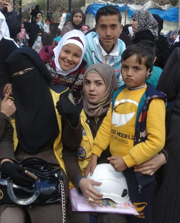 فاطمة عارف مع ابنيها وبنها الثلاثة وصديقتها خلال حملة في أحد مخيم بريف اللاذقية