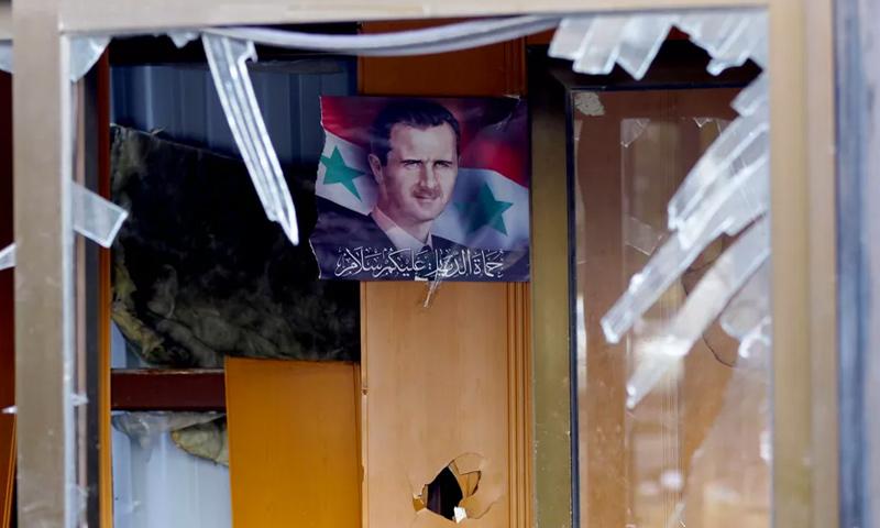 صورة لرئيس النظام السوري بشار الأسد في بناء متضرر في دمشق - 9 شباط 2016 (AFP)