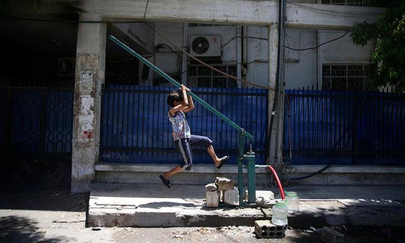 طفل يشد ذراعًا لجر المياه من بئر يدوي في الغوطة الشرقية- 2016 (رويترز)