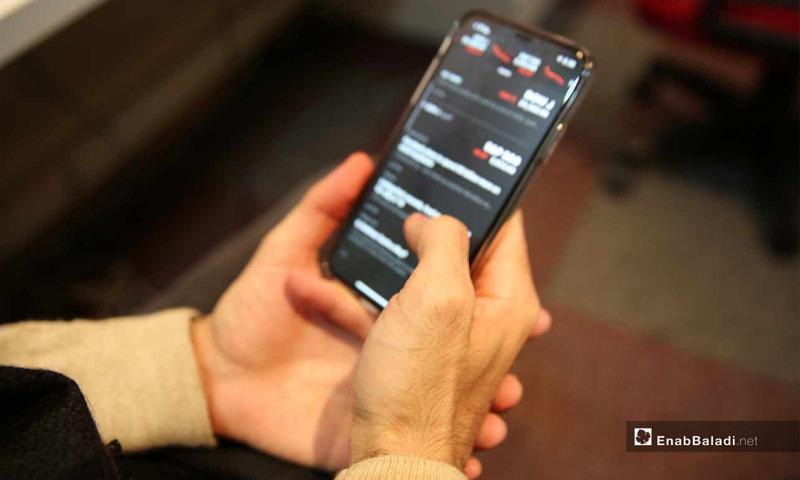 تعبيرية: رجل يحمل هاتفه الجوال (عنب بلدي)