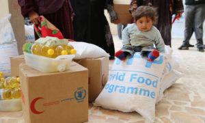 فتاة صغيرة تجلس على المساعدات الغذائية المقدمة من برنامج الغذاء العالمي في دمشق - 2014 (WFP)