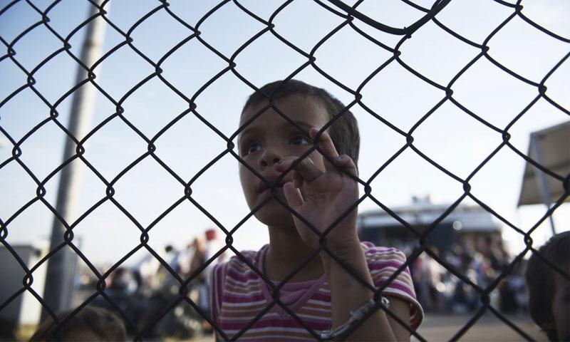 فتاة مهاجرة تنظر عبر سياج شمال اليونان - 2 أيلول 2019 (AP)