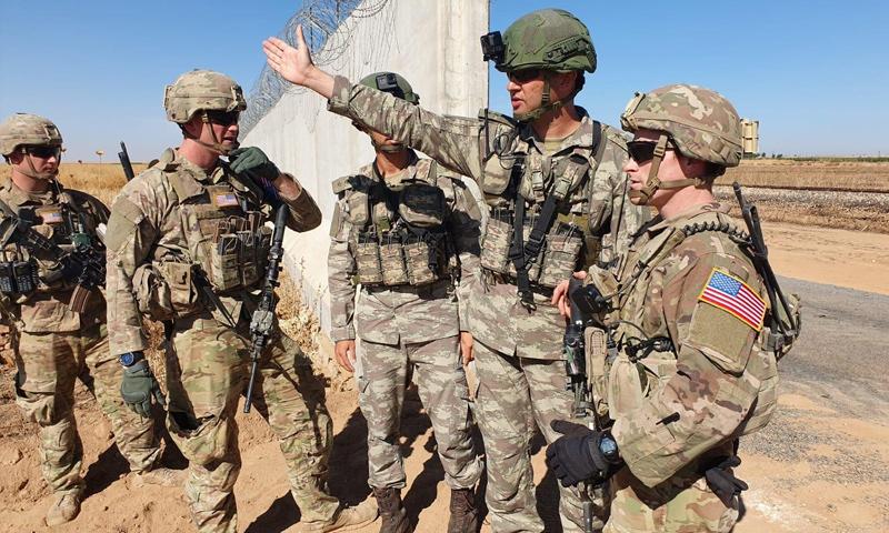 جنود أتراك وأمريكيون على الحدود السورية التركية في أثناء تسيير دورية برية شمالي سوريا - (رويترز)
