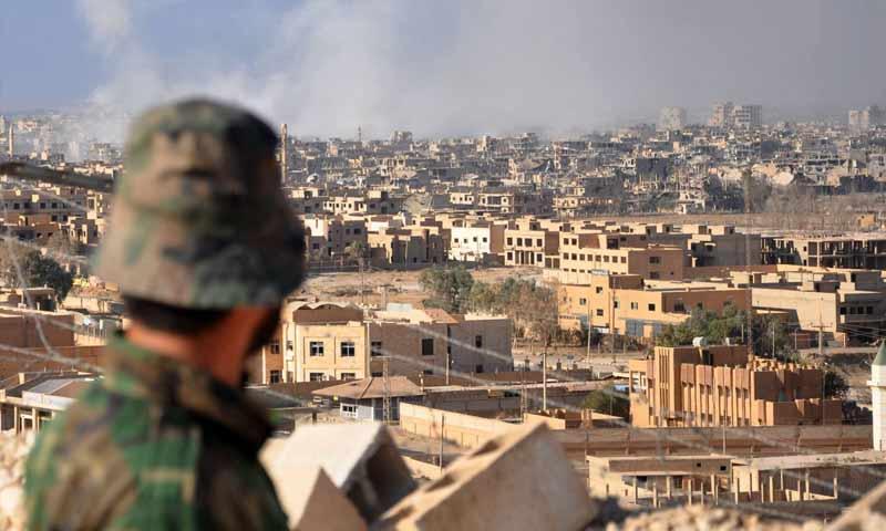 مقاتل من قوات النظام السوري يقف على الجبل المطل على مدينة دير الزور (AFP)