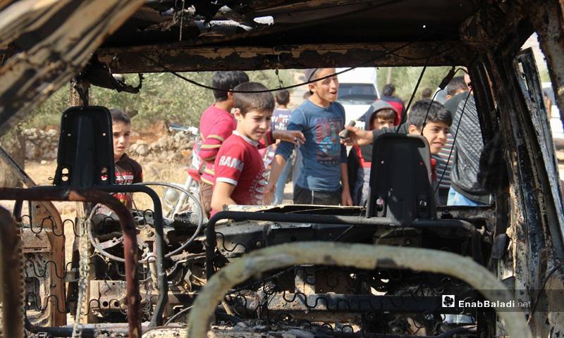أطفال بالقرب من سيارة محترقة جراء الإنزال الأمريكي في باريشا بمحافظة إدلب- 27 من تشرين الأول 2019 (عنب بلدي)