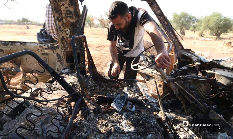 شخص ينظر إلى باص محترق جراء استهدافه خلال عملية الإنزال الأمريكي في باريشا بمحافظة إدلب- 27 من تشرين الأول 2019 (عنب بلدي)
