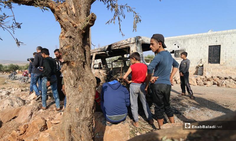 أطفال بالقرب من  باص محترق جراء استهدافه خلال عملية الإنزال الأمريكي في باريشا بمحافظة إدلب- 27 من تشرين الأول 2019 (عنب بلدي)