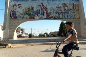 طفل يركب دراجته الهوائية أمام لافتة لصور رئيس النظام السوري بشار الأسد والده حافظ في محافظة درعا جنوبي سوريا (AFP)