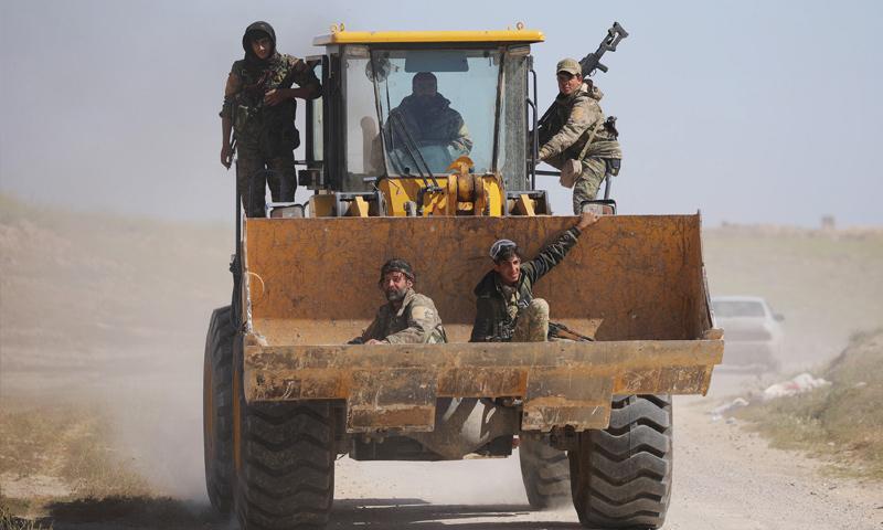 مقاتلون من قسد يجلسون في دلو حفارة في قرية باغوز بريف دير الزور – آذار 2019 (رويترز)