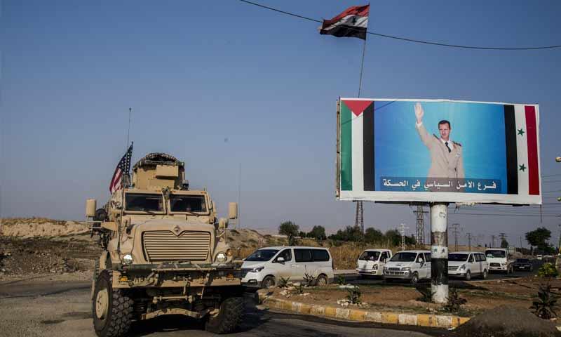 قافلة عسكرية أمريكية تحمل العلم الأمريكية تمر بجنب صورة لرئيس النظام السوري بشار الأسد في الحسكة- 26 من تشرين الأول 2019 (AP)