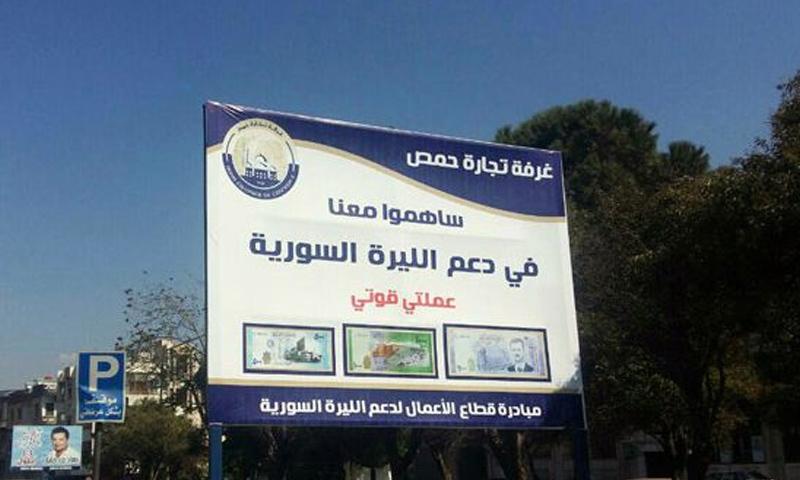 لافتة طرقية في مدينة حمص تدعو للمشاركة في مبادرة دعم الليرة السورية - (ٍسانا)