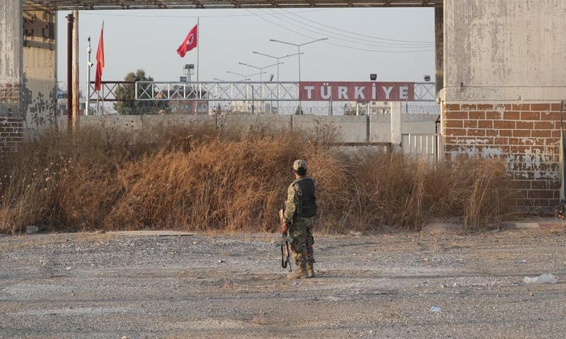 """مقاتل من """"الجيش الوطني"""" يقف على الحدود السورية-التركية بالقرب من مدينة تل أبيض (رويترز)"""