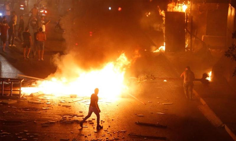 محتجون في بيروت يضرمون النيران احتجاجاً على الأوضاع المعيشية - (رويترز)