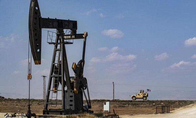 مركبة عسكرية أمريكية تمر عبر رافعة لضخ النفط في ريف مدينة القامشلي بشمال شرق سوريا في-26 من تشرين الأول 2019 (AFP)