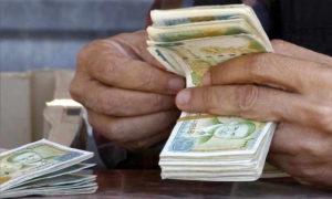 تاجر عملة يعد أوراق نقدية لليرة السورية (رويترز)